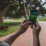 "A woman holds up her cell phone as she plays the Pokemon Go game in Lafayette Park in front of the White House in Washington, DC, July 12, 2016. Pokémon Go mania is sweeping the US as players armed with smartphones hunt streets, parks, rivers and elsewhere to capture monsters and gather supplies in the hit game. The free application based on a Nintendo title that debuted 20 years ago has been adapted to the mobile internet Age by Niantic Labs, a company spun out of Google last year after breaking ground with an ""Ingress"" game that merged mapping capabilities with play. As of July 11, 2016 Pokémon Go had been downloaded millions of times, jumping topping rankings at official online shops for applications tailored for smartphones powered by Apple or Google-backed Android software.   / AFP / JIM WATSON        (Photo credit should read JIM WATSON/AFP/Getty Images)"